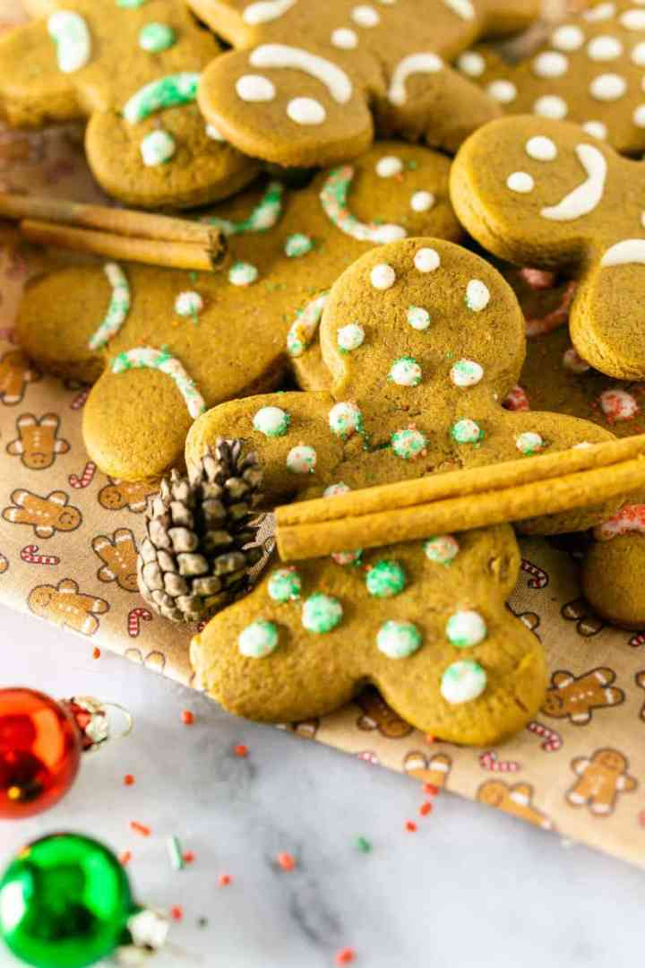 A gingerbread man cookie with a cinnamon stick.