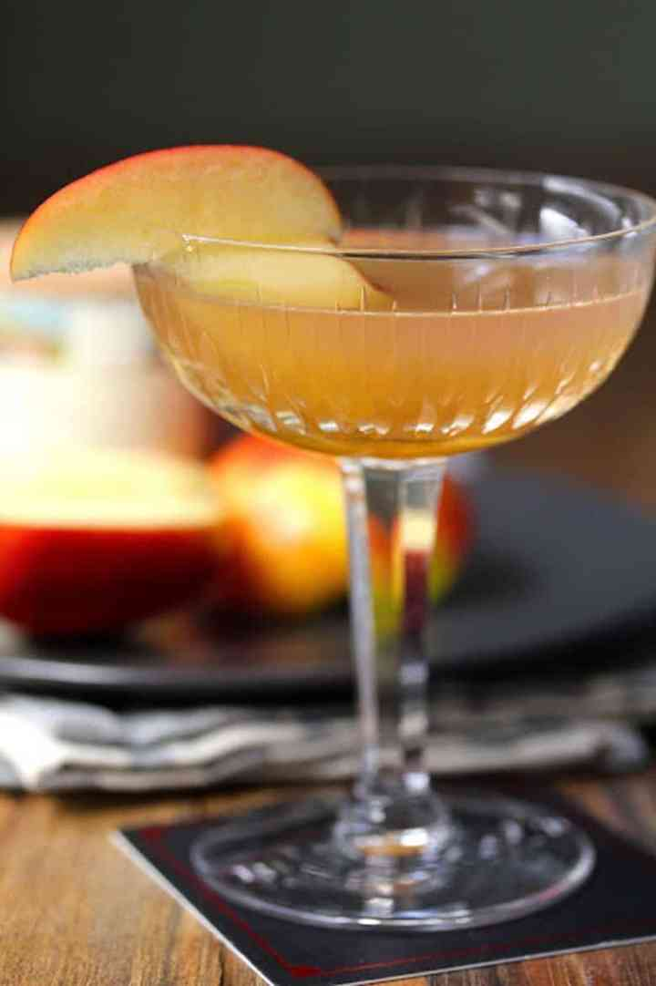 An Apple Brown Derby Cocktail with apple slices in the background.