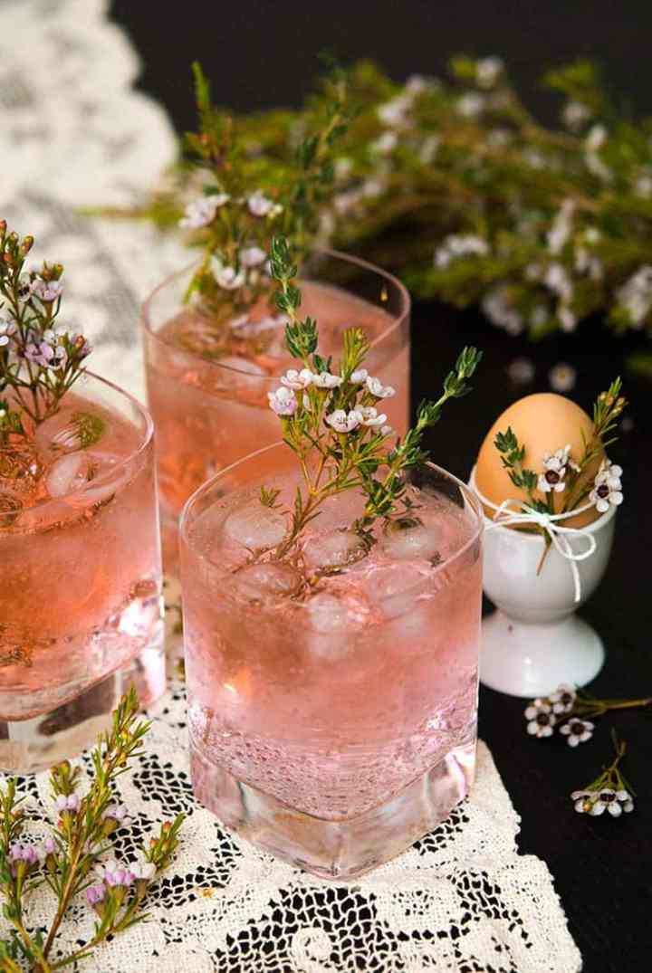 Three pink gin and tonics with a flower garnish.