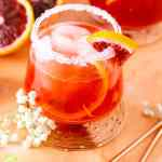 A blood orange margarita with cut-up blood oranges.