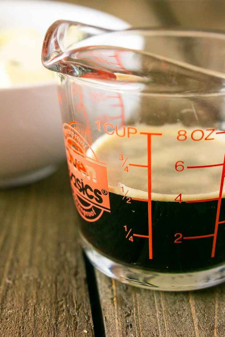 A measuring cup of beer ready to use for the brownie batter.