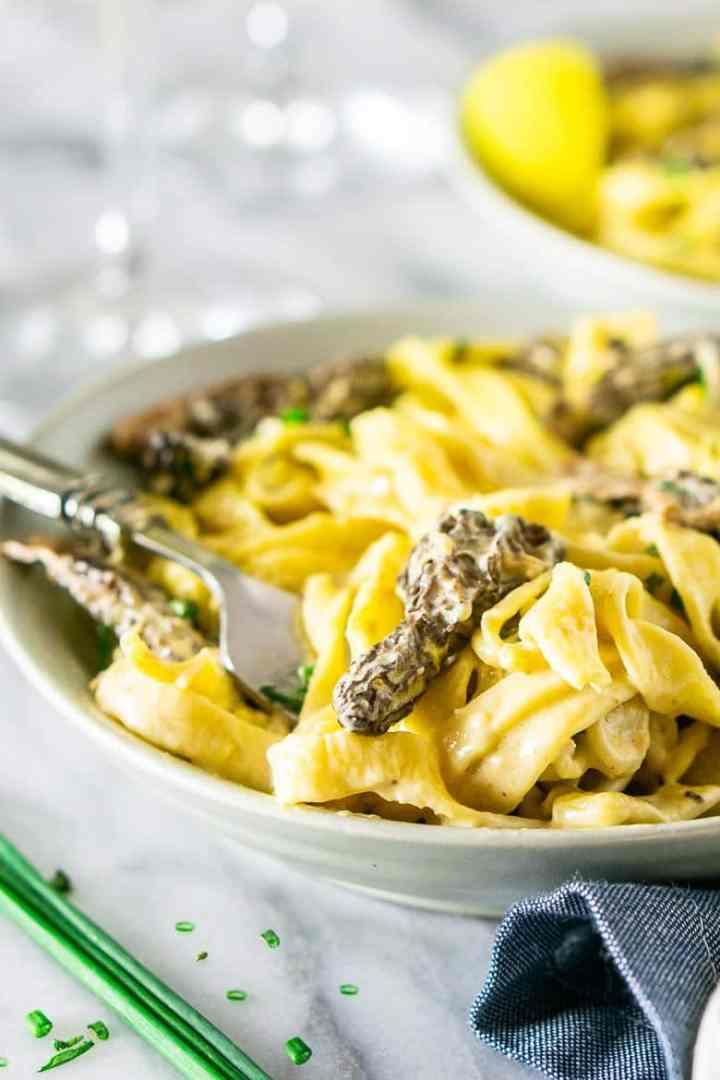 A fork swirling into the morel mushroom pasta.