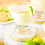 Two sparkling key lime pie martinis with graham crackers and key limes.