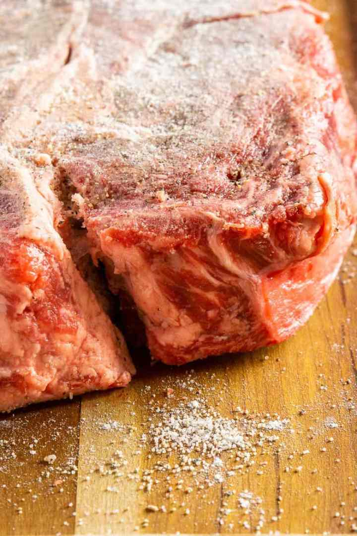 The chuck roast dusted with flour, salt and pepper sitting on a wooden cutting board.