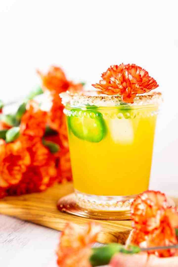 A single jalapeno-mango margarita with flowers all around.