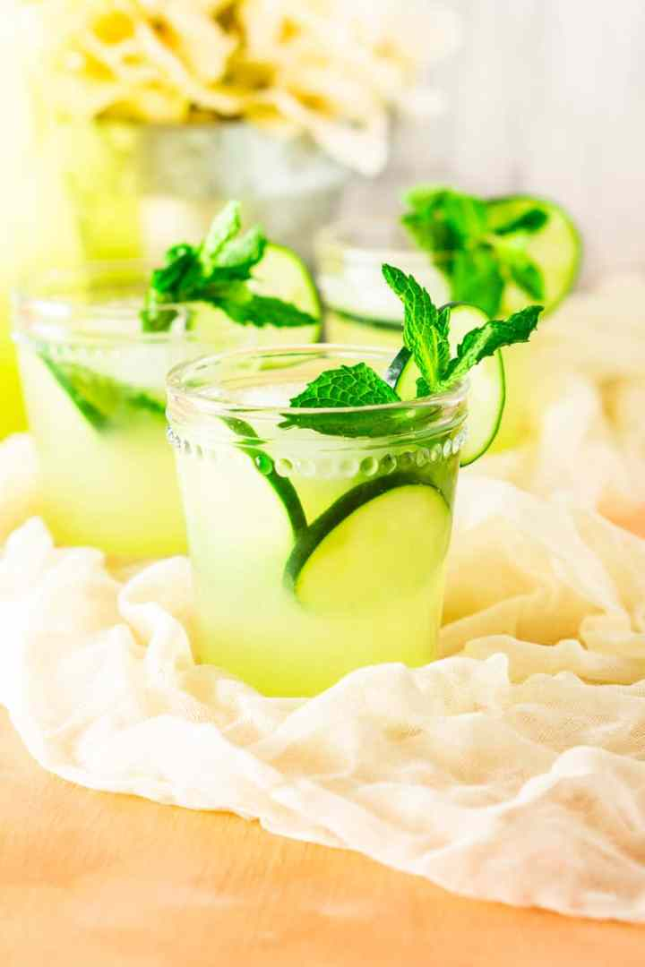 A closeup of one mint-cucumber lemonade with other glasses in the background.