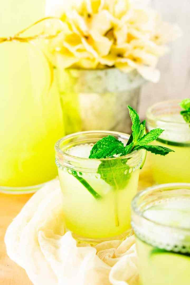 A glass of mint-cucumber lemonade with flowers in the background.