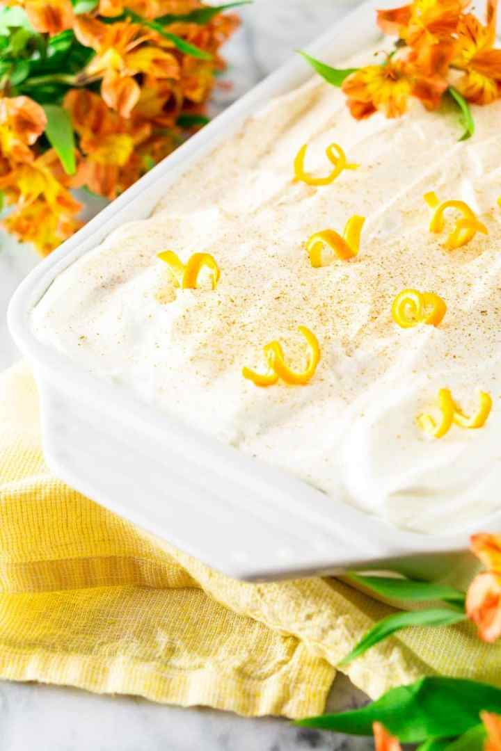A pan of spiced orange tres leches cake on a yellow napkin with flowers.