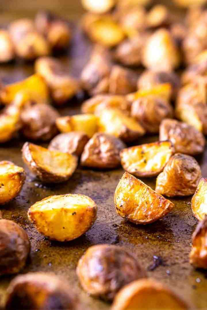 A sheet pan of the potato chunks roasted until crispy for the herbed roasted potato salad.