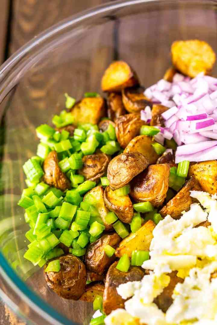 A bowl of roasted potatoes, celery, red onions and chopped eggs.