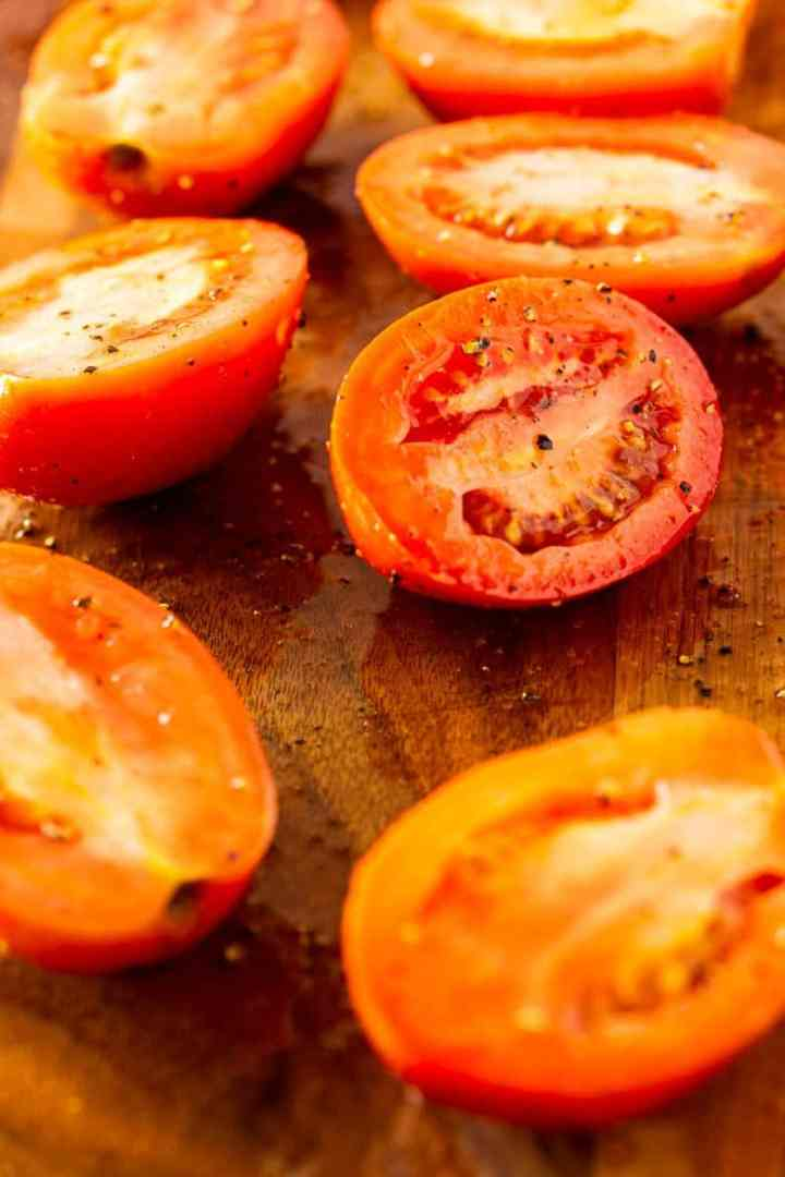 Sliced tomatoes on a cutting board ready to roast.
