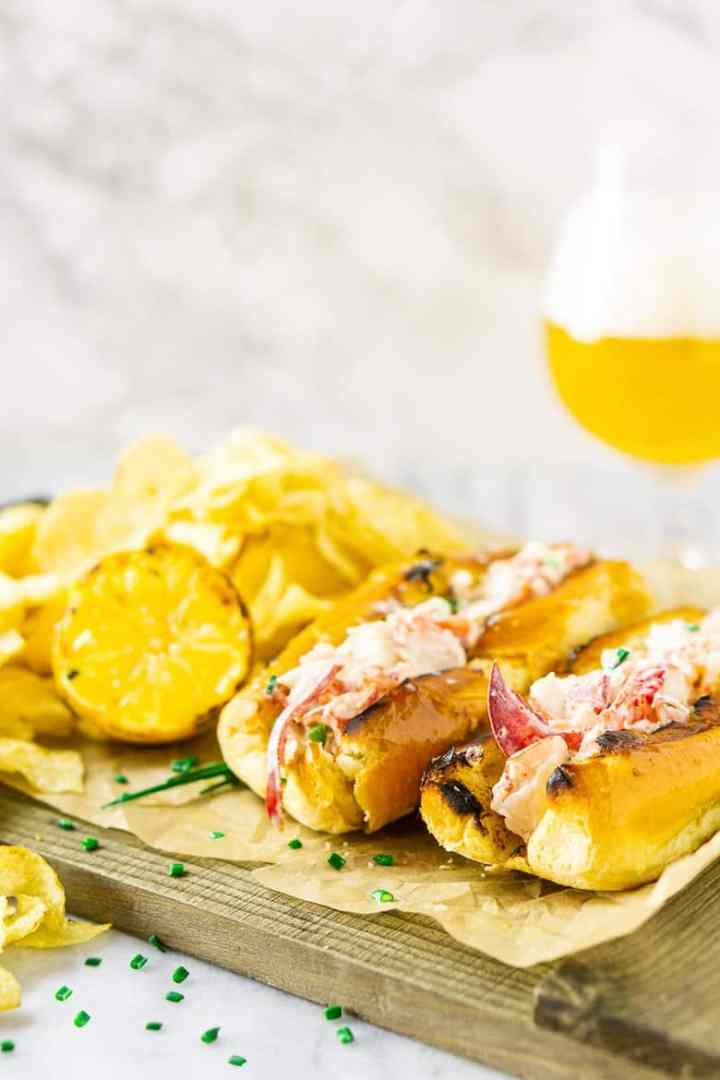 Two Maine-style lobster rolls on parchment paper with a beer in the background.