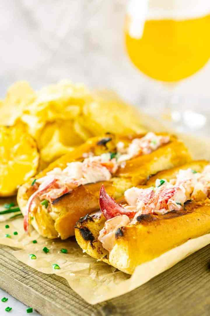Two Maine-style lobster rolls with a pile of chips and lemon.