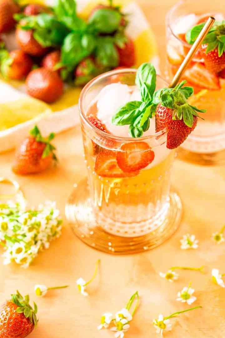 Looking down into a strawberry-basil Tom Collins with fresh strawberries and basil.
