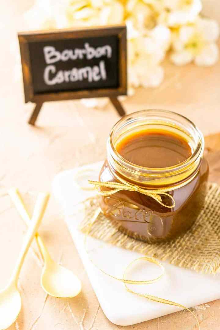 A jar of bourbon caramel sauce from up top on burlap and a marble tray.