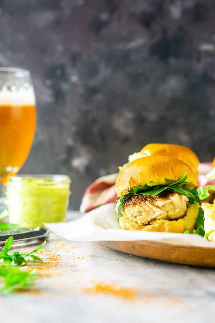 A front view of a crab cake slider with Old Bay seasoning and a beer.