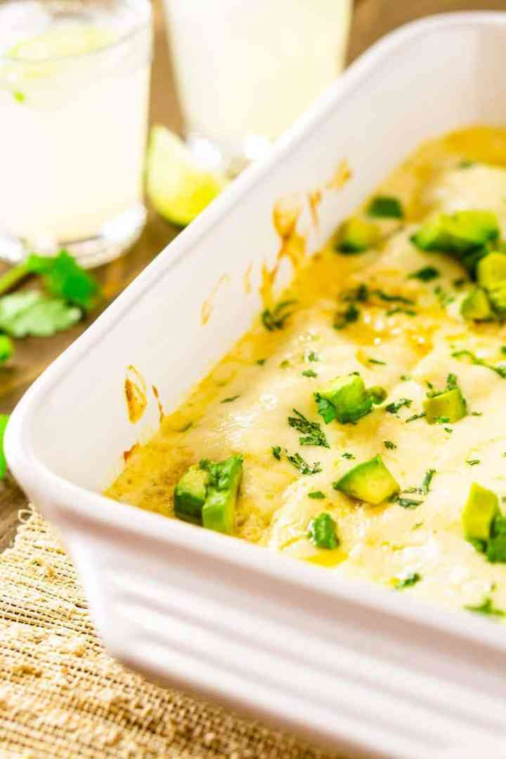 A closer side view of a pan of jerk chicken enchiladas smothered in sour cream sauce.