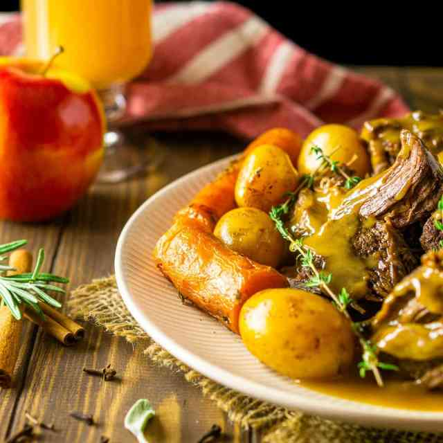 A plate of apple cider pot roast with gravy and a glass of apple cider with an apple in the background.