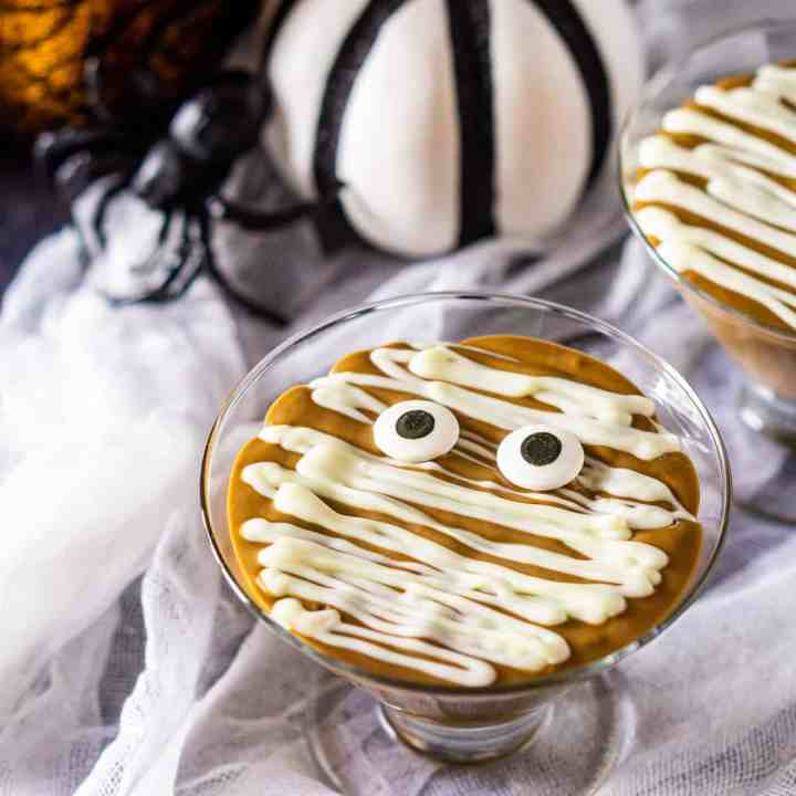 Two mummy pudding cups with pumpkins and a decor spider in the background.