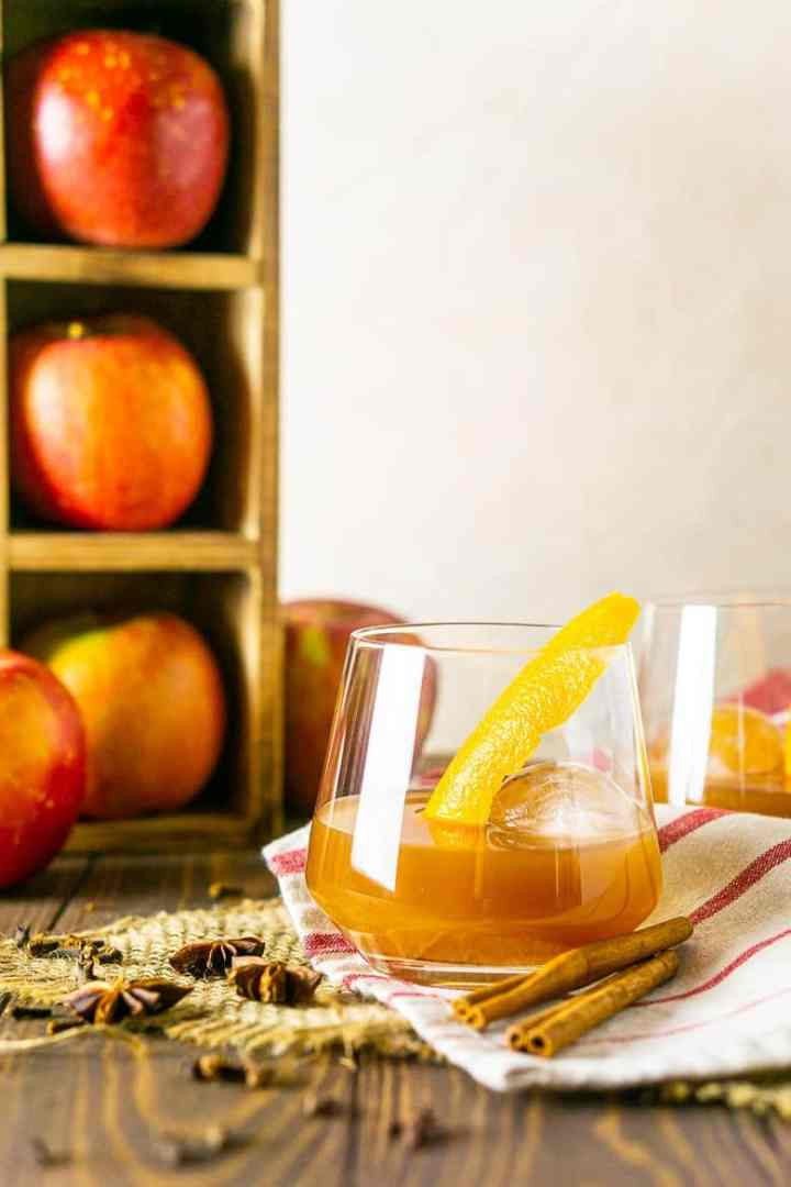 Looking straight on to an apple cider old fashioned with apples in the background.