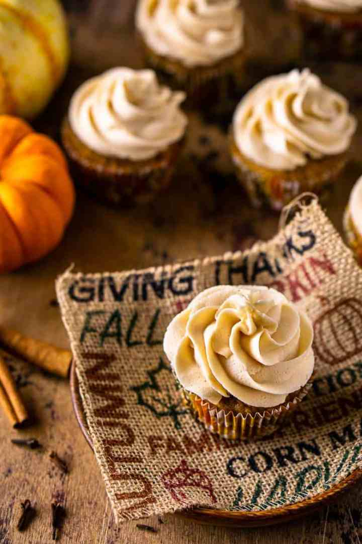 An aerial view of the brown butter-pumpkin cupcakes with two pumpkins in the background.