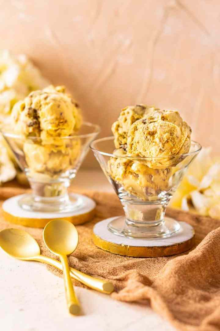 Two ice cream dishes of butterscotch ice cream with candied pecans on gold and marble coasters.