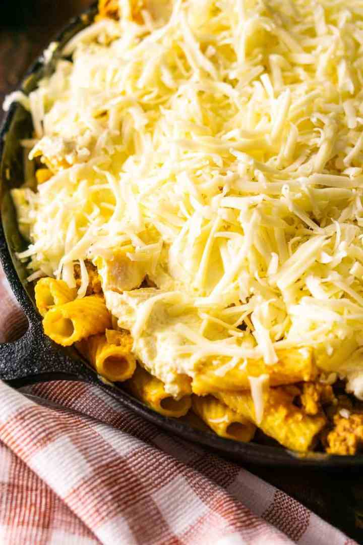 Topping the chorizo and pumpkin baked ziti with shredded fontina.