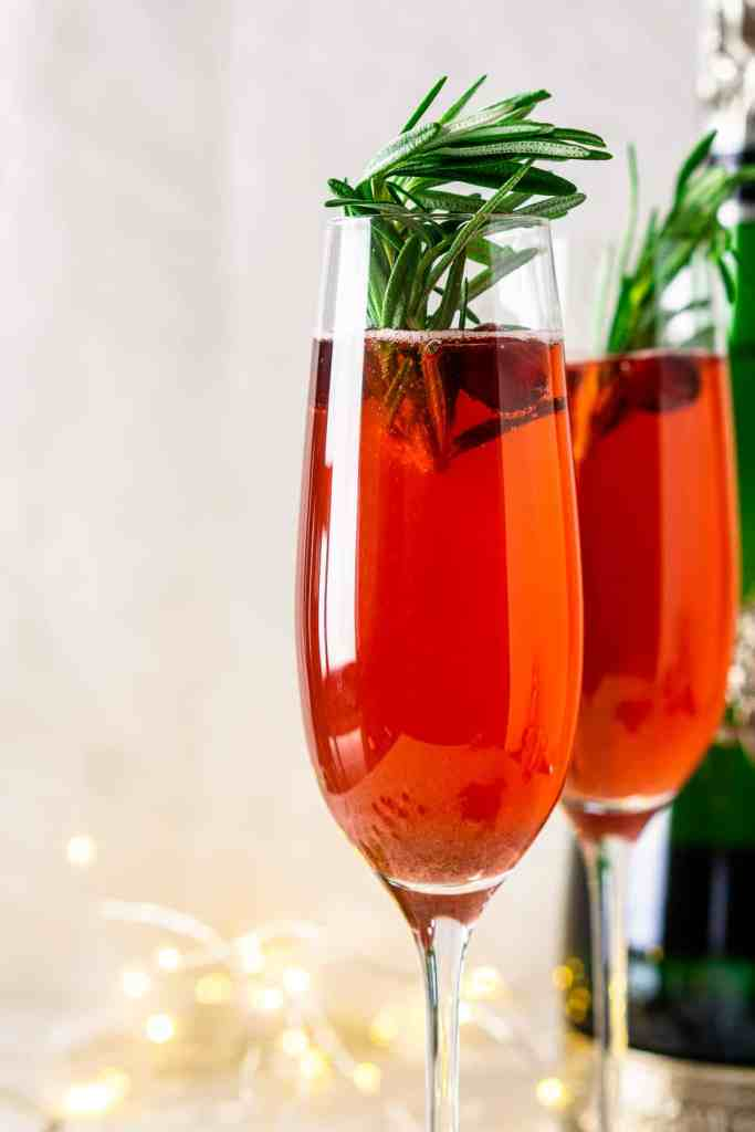 A close-up view of a cranberry-spice Christmas mimosa with lights in the background.