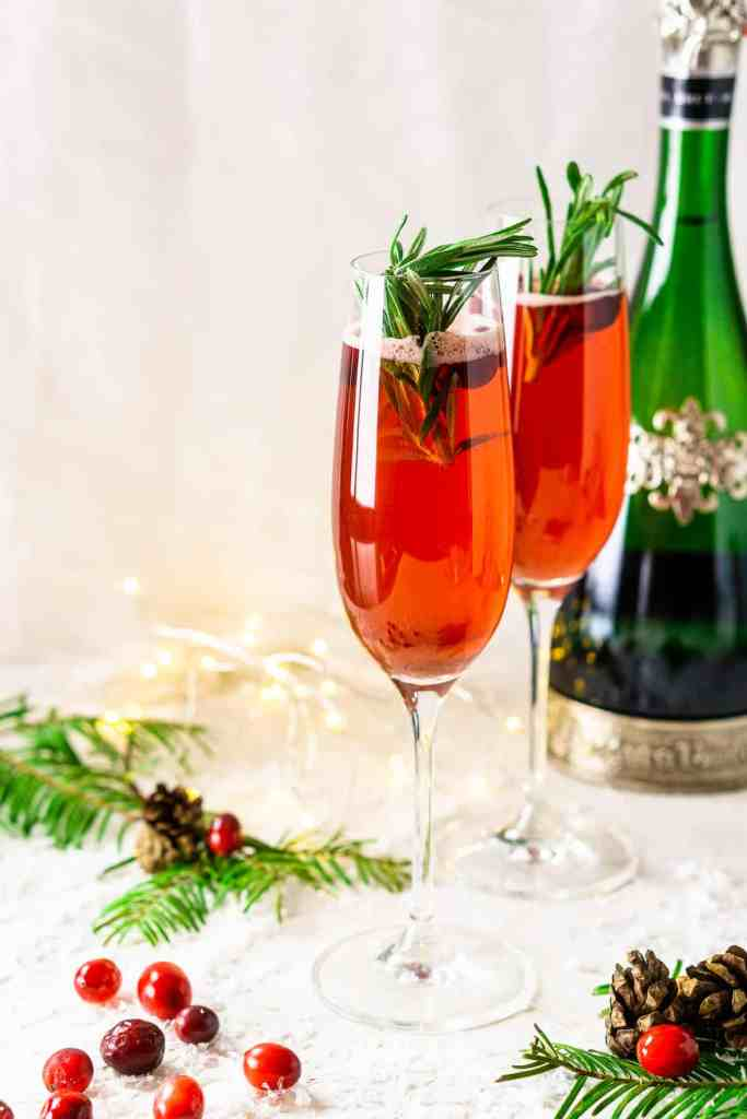 Two cranberry-spice Christmas mimosas with a bottle of Champagne in the background with lights and fresh cranberries.