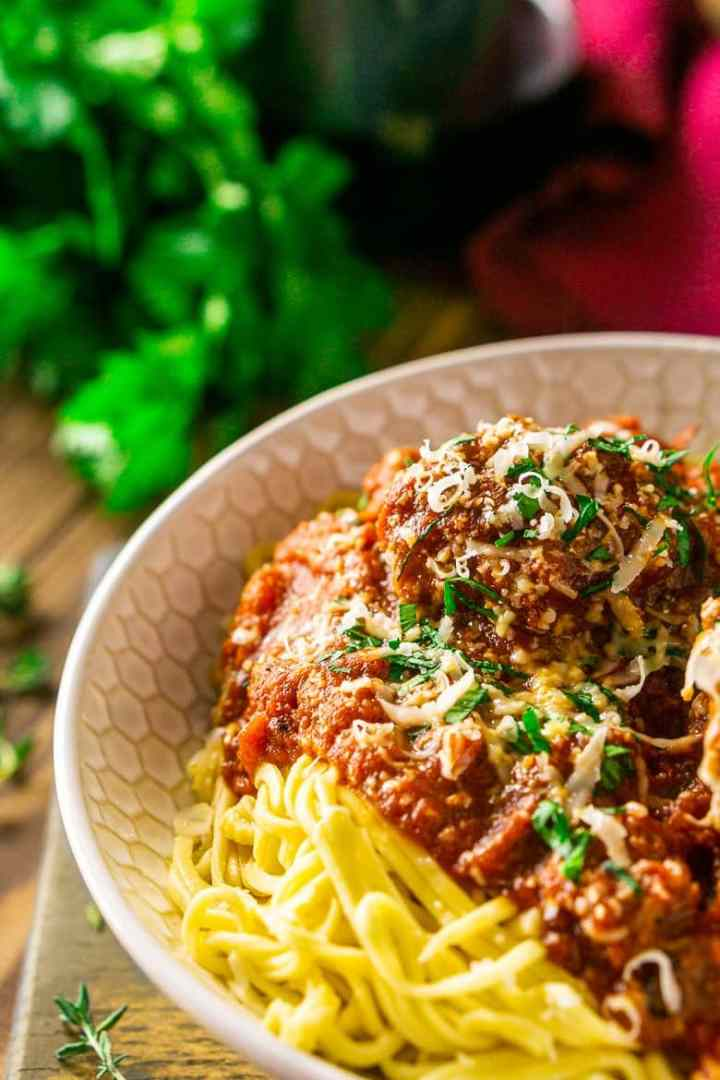 A close-up shot of a bowl of Italian meatballs and spaghetti with a bunch of fresh parsley.