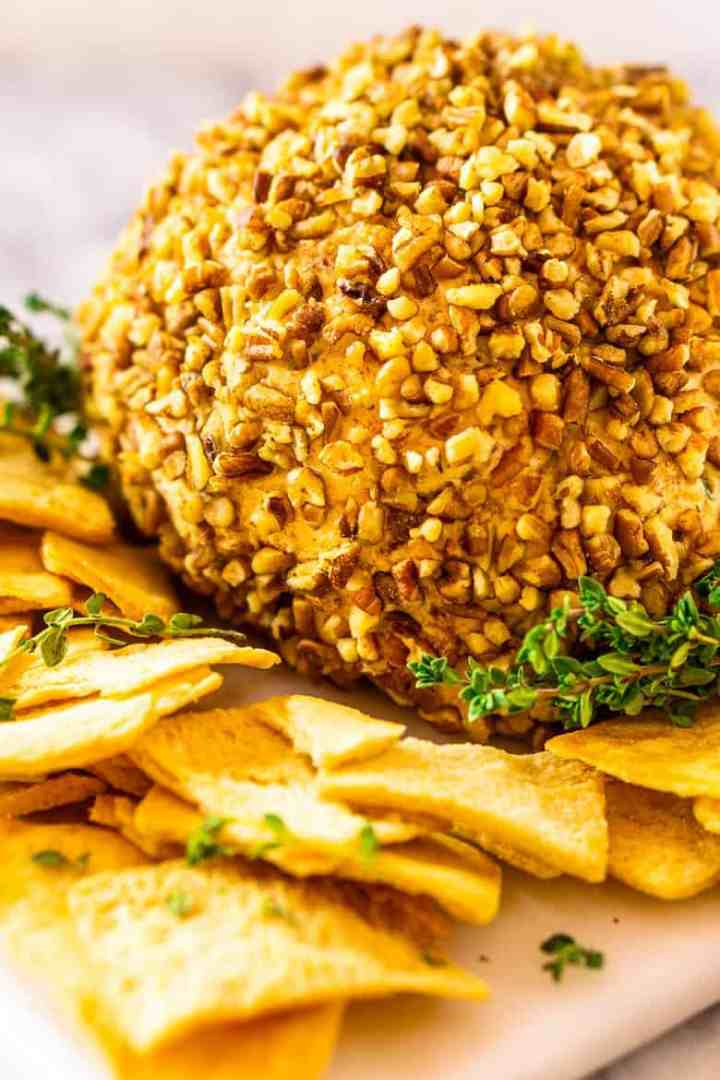The bourbon bacon cheese ball on a white plate with pita chips surrounding it.