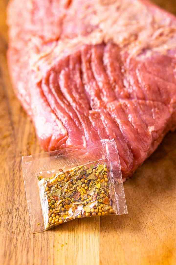 A slab of corned beef on a cutting board with the seasoning packet.