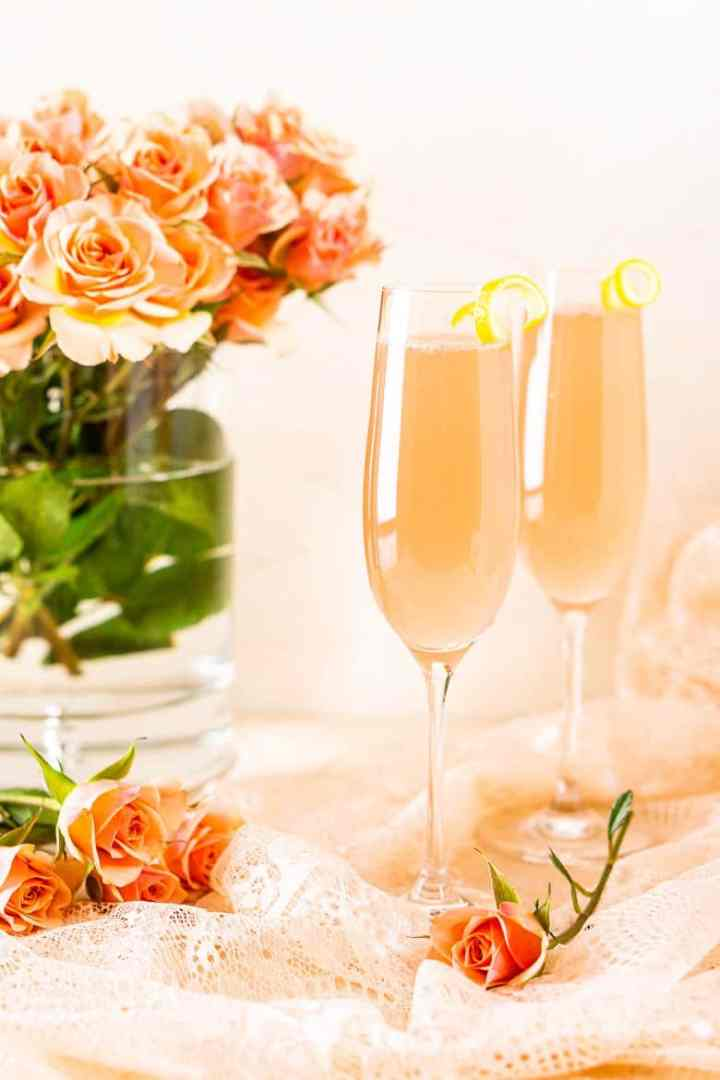 Two sparkling rosé French 75 cocktails on pink lace with roses in the background.
