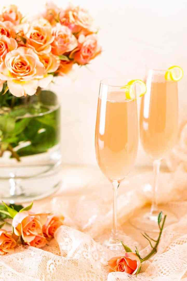 Two rosé French 75 cocktails on lace with roses on the sides.