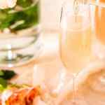 Pouring the wine into a flute of the sparkling rosé French 75 with pink roses in the background.