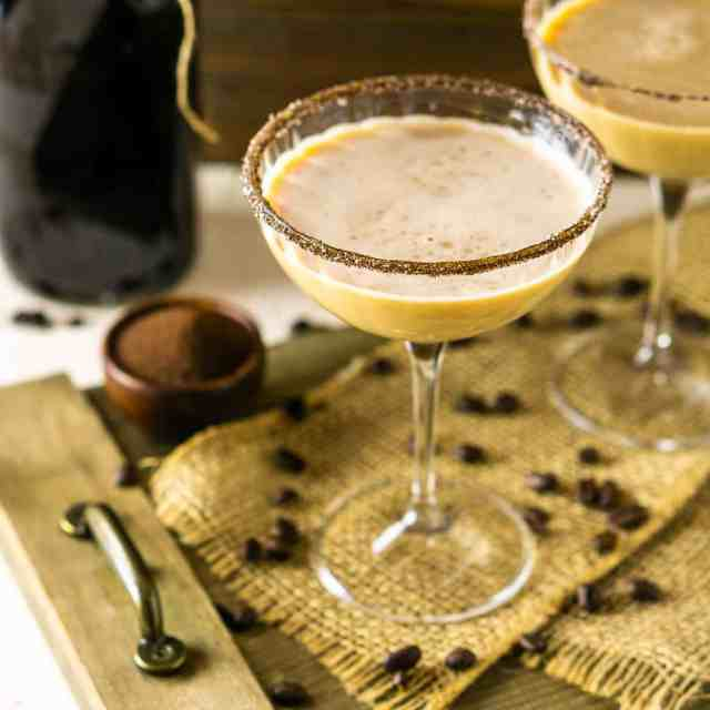 A Baileys Irish coffee martini in a coupe glass on burlap and a wooden platter.