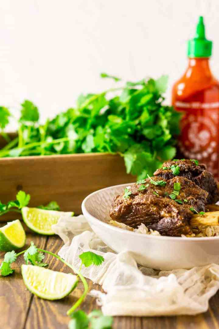 Looking straight on to a bowl of sriracha short ribs with cilantro and hot sauce in the background.