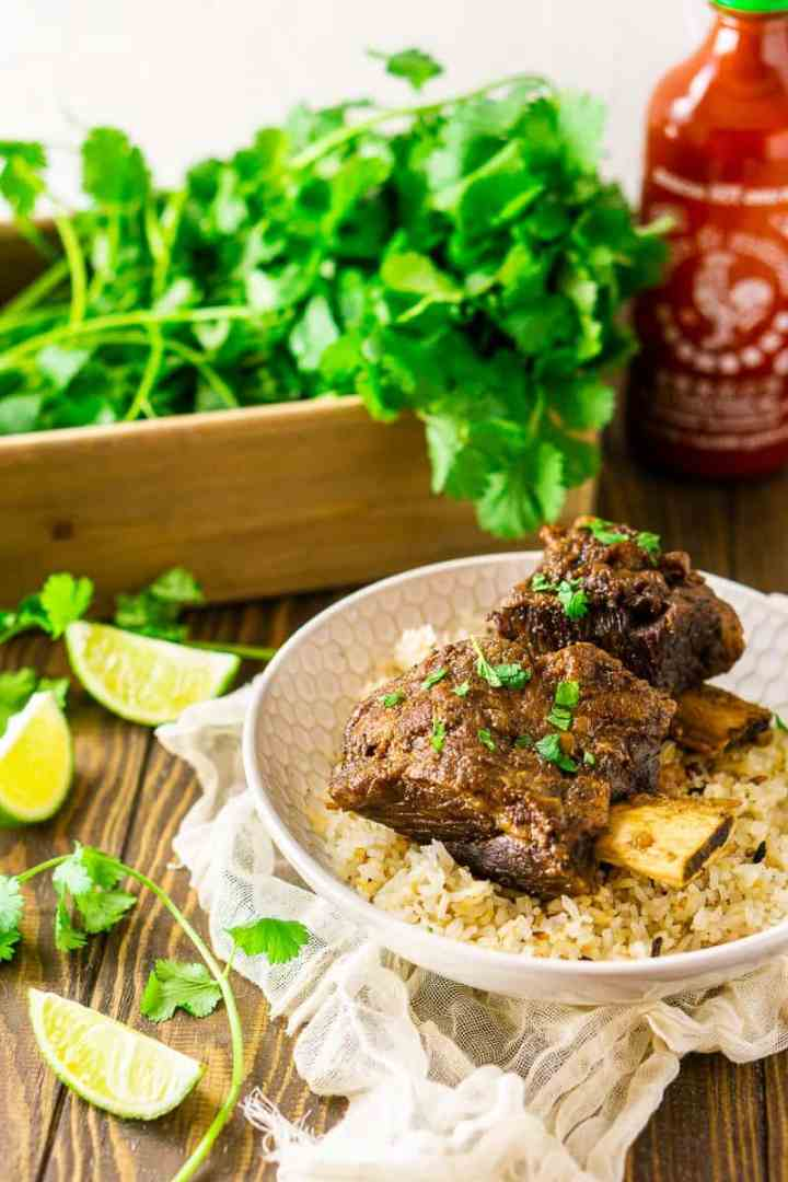 Looking down from an aerial view of two Asian-inspired short ribs with a bottle of sriracha.