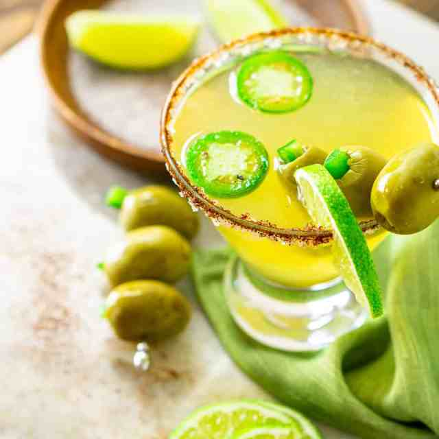 A spicy Mexican martini on a marble platter with garnishes around it.