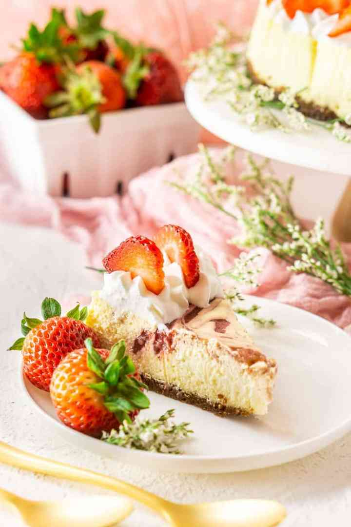 A slice of the fresh strawberry-ginger cheesecake with strawberries, flowers and the whole cheesecake in the background.