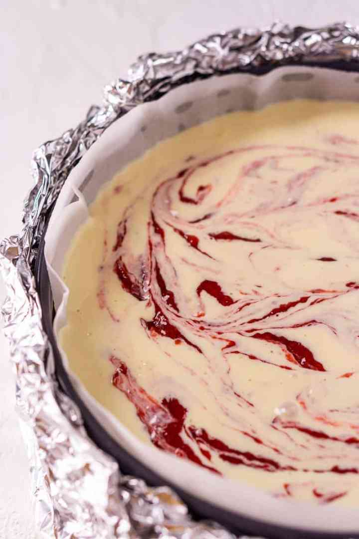 The strawberry-ginger sauce swirled into the cheesecake batter in a springform pan.