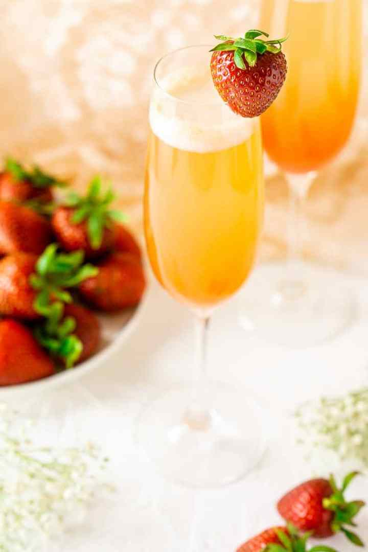 A close-up of a strawberry-rhubarb mimosa with flowers and strawberries.