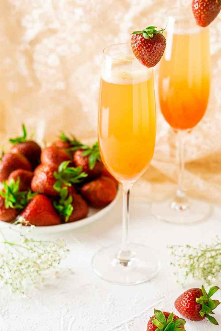 Two strawberry-rhubarb mimosas on a white background with strawberries on a white plate.