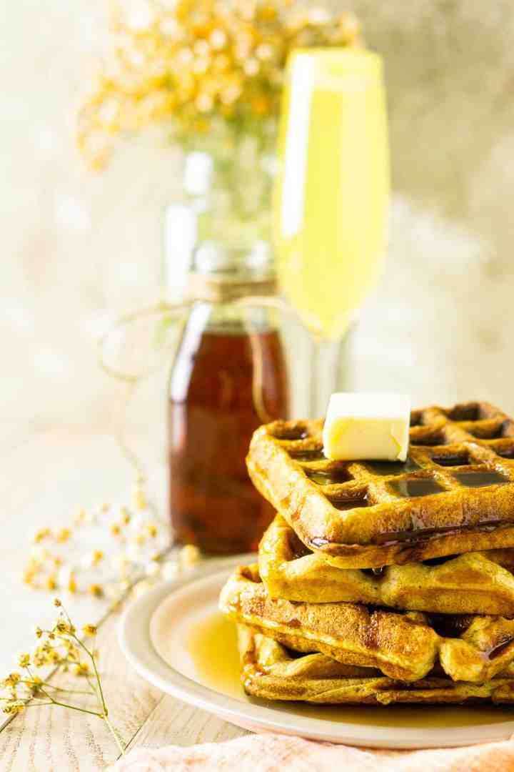 A side view of the buttermilk waffles with flowers and a mimosa.