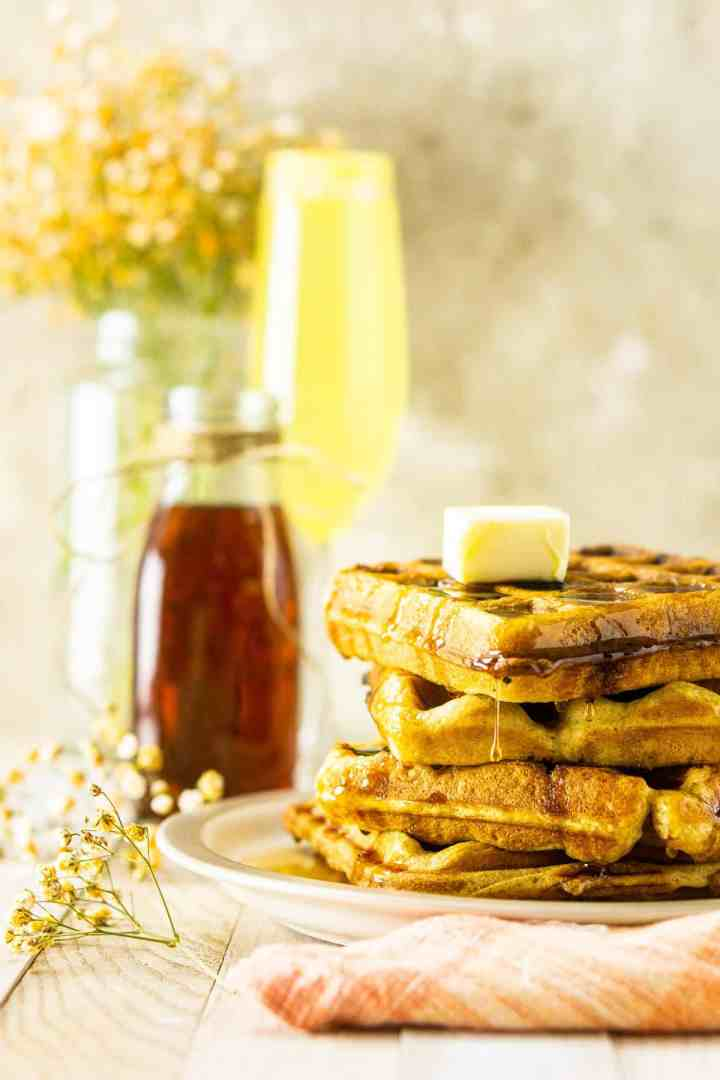 A stack of buttermilk waffles with syrup running off the side.