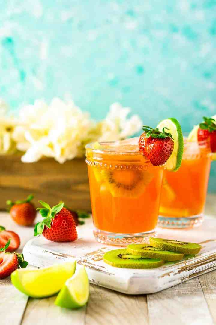 The strawberry-kiwi margarita against a blue background with fruit and flowers around it.