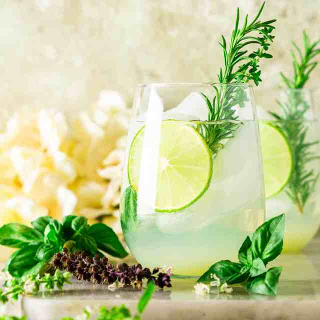 A garden gin and tonic with a rosemary sprig garnish and fresh herbs surrounding it.
