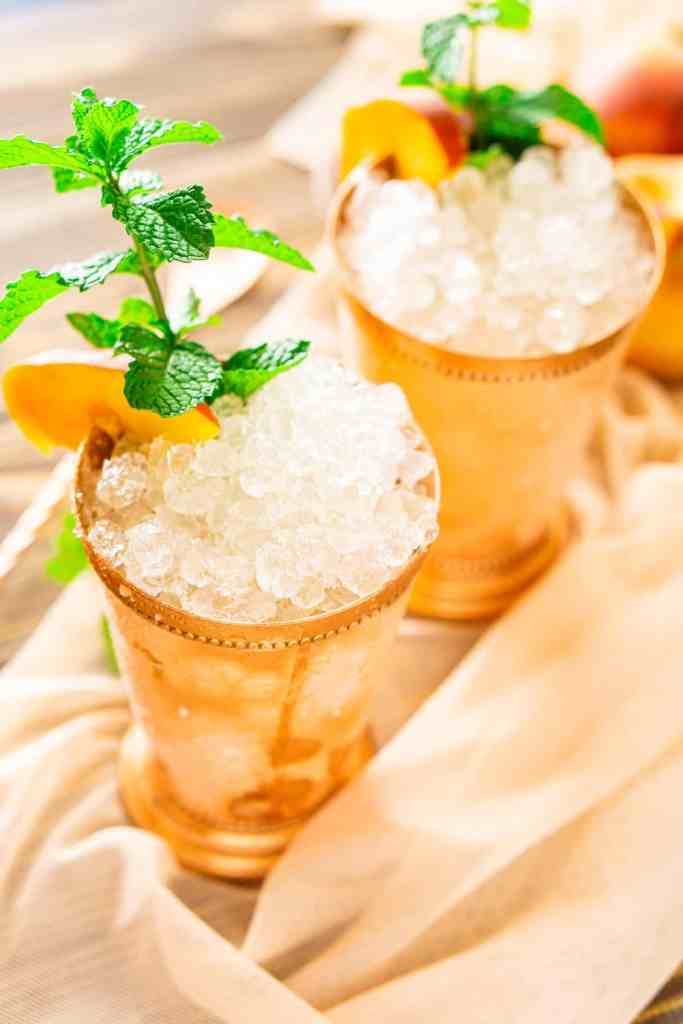 Looking down on two peach mint juleps on sheer fabric with soft lighting in the background.