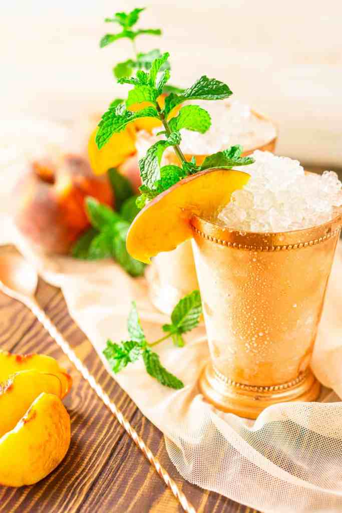 The peach mint juleps with a bunch of whole peaches in the background on sheer fabric.