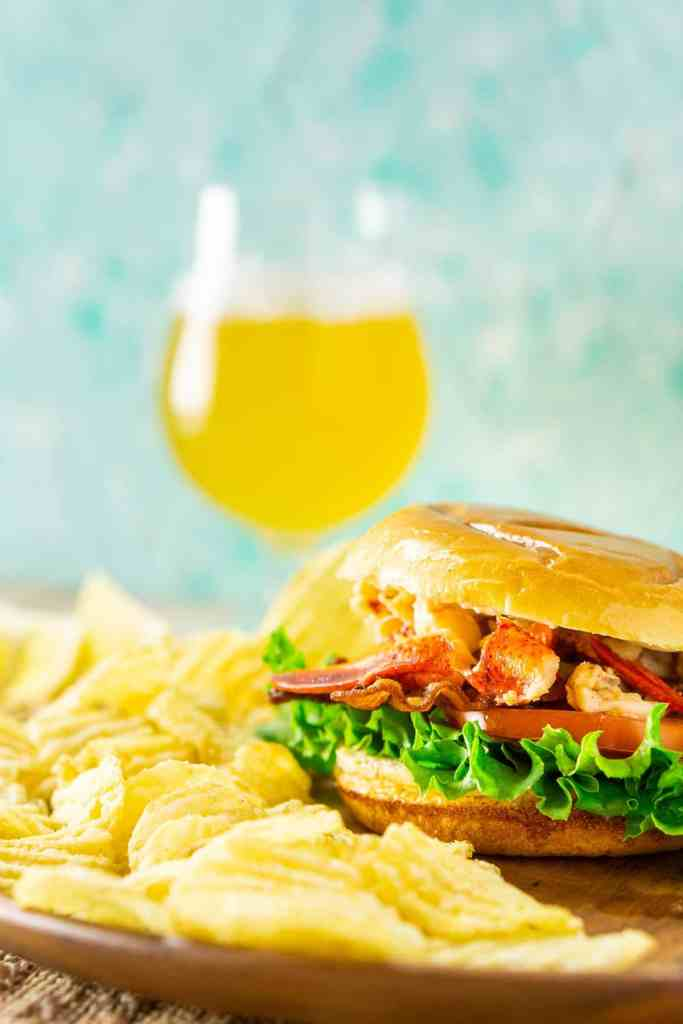 A close-up view of a Connecticut lobster BLT with chips on the side on a wooden plate.